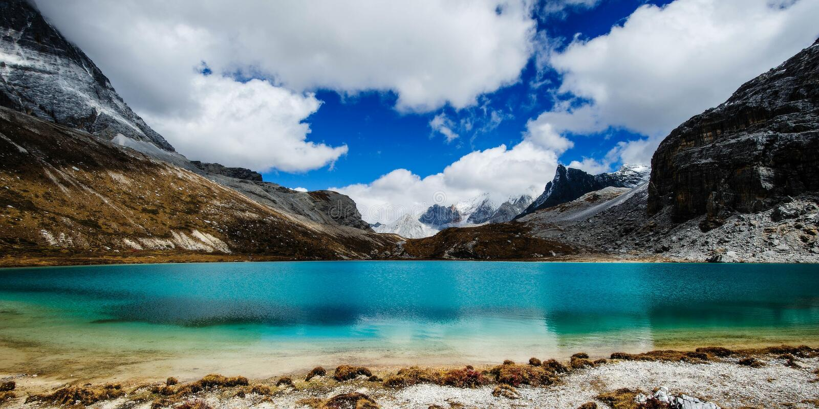 Milk lake in highland around by snow mountains under blue sky royalty free stock photography