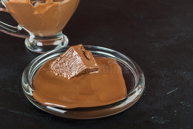 Milk molten chocolate on plate with glass jar. On black backgrund royalty free stock photo