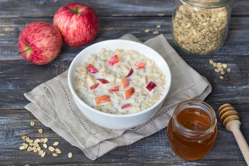 Milk oatmeal porridge with apple and honey in white bowl on wooden table. Delicious healthy homemade breakfast royalty free stock image