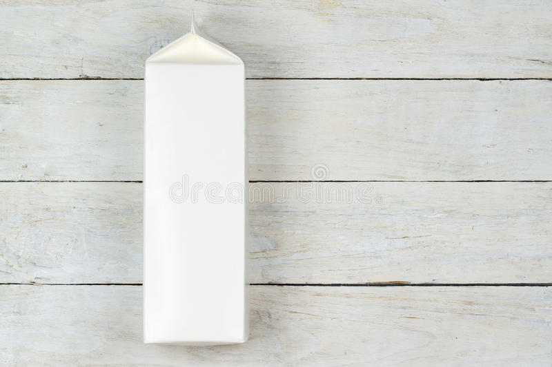 Milk pack. Blank cardboard milk pack on wooden table stock photos