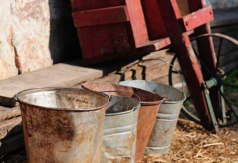 Milk pails on a farm. Several milk pails near a wheel barrow on a dairy farm royalty free stock image