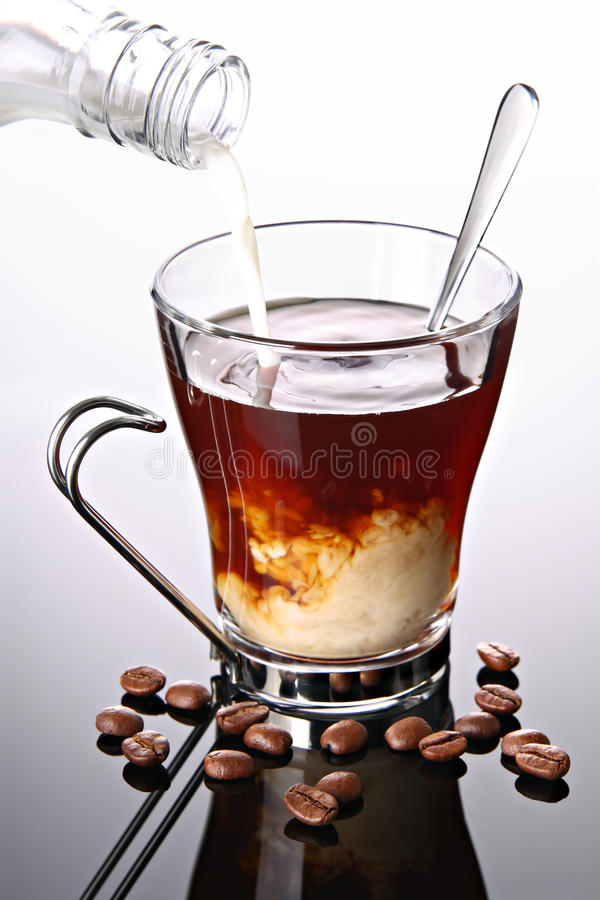 Milk poured into cup of coffee royalty free stock photo