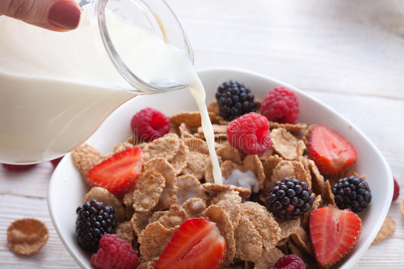 Milk pouring into bowl of cereals with fresh berries stock photography