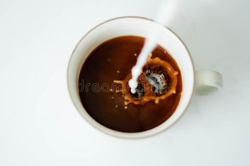Milk pouring into coffee stock photography