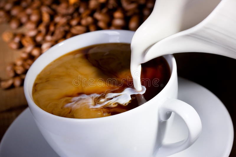 Milk pouring into cup. Of coffee stock images
