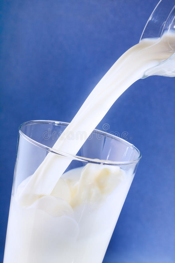 Milk pouring into glass royalty free stock photo