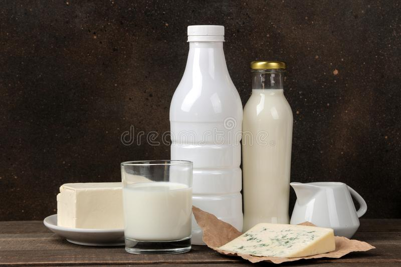 Milk products. milk, sour cream, cheese, butter and cottage cheese on a brown wooden table stock image