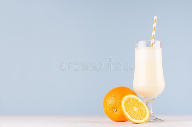 Milk shake alaranjado fresco da mola com as laranjas suculentas das fatias, palhas listradas no fundo azul macio, espaço da cópia fotos de stock