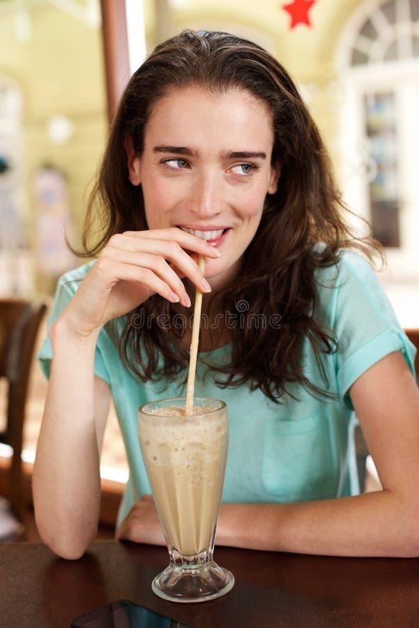 Milk shake bebendo da jovem mulher em um café fotografia de stock royalty free