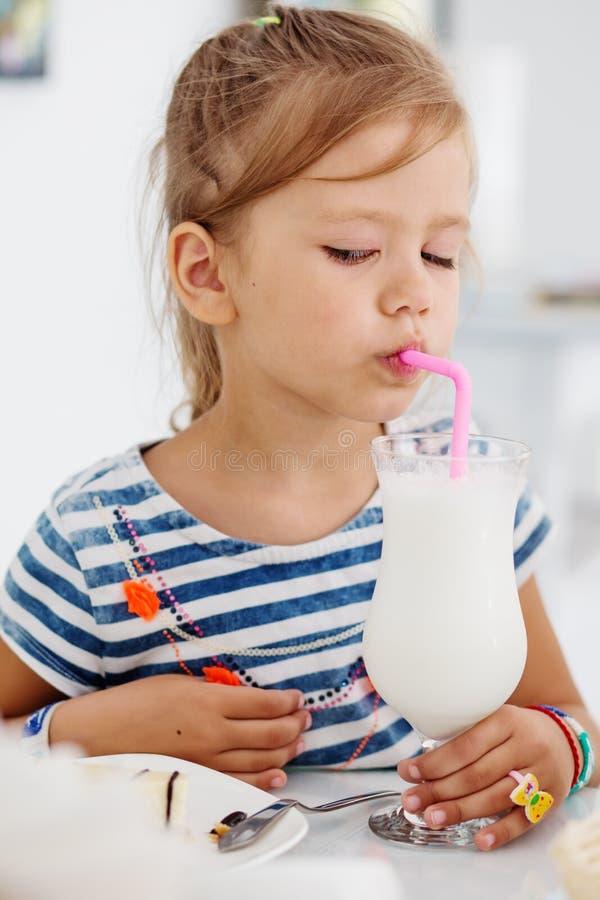Milk shake bebendo da menina adorável fotos de stock