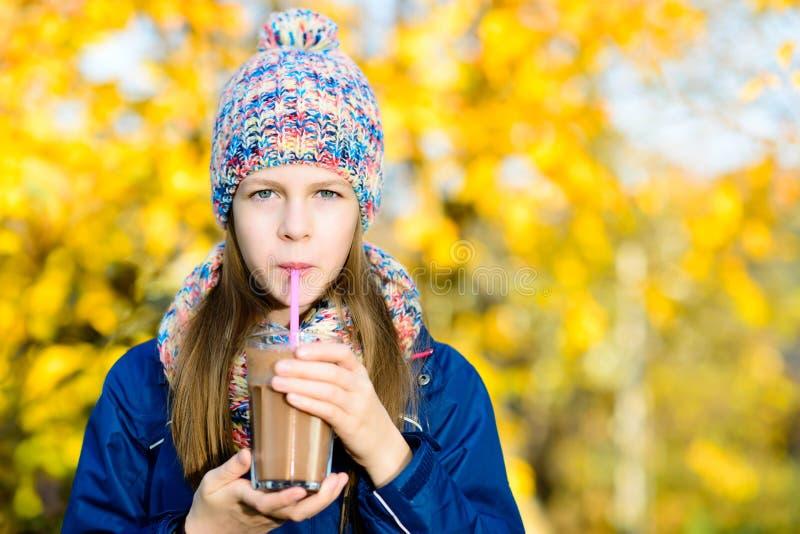 Milk shake bebendo do chocolate da moça no parque do outono imagem de stock