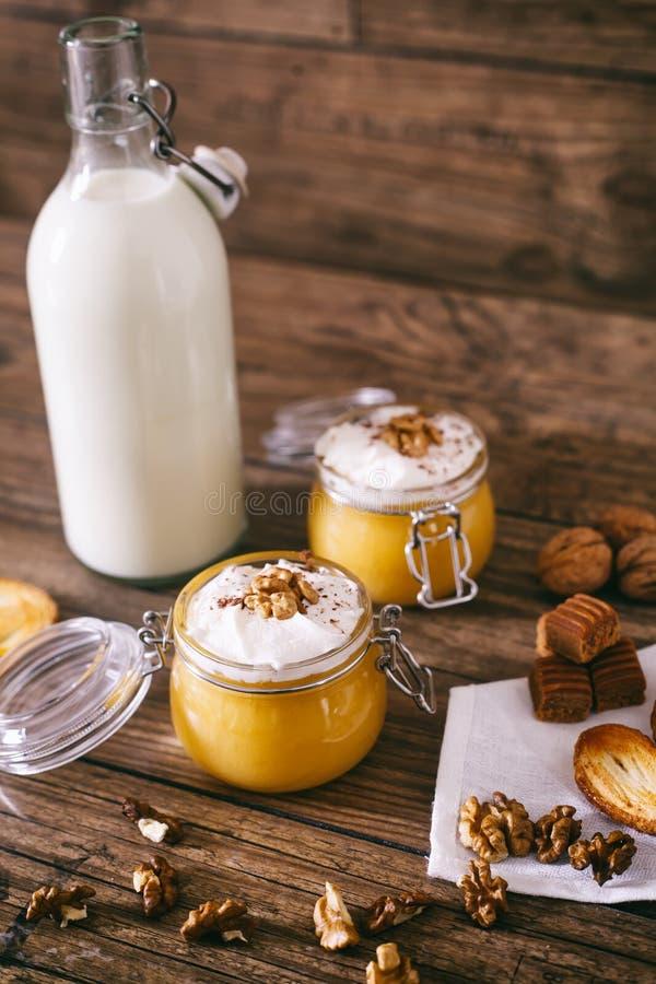 Milk shake da abóbora no frasco de vidro com as cookies do chantiliy, do caramelo, da noz e do mel Frasco do leite De madeira esc fotografia de stock