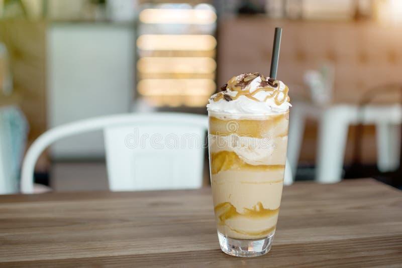 Milk-shake glacé avec le sirop fouetté de crème et de caramel, avec des pailles et des grains de café dans un verre grand sur la  images stock