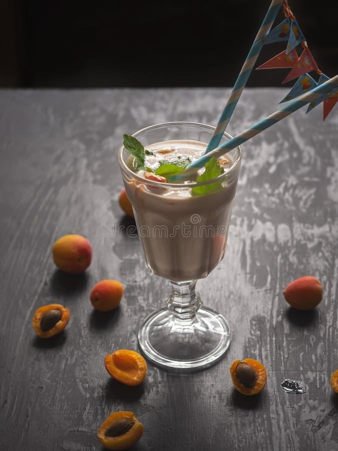 Milk shake grosso com fruto, abricós e banana em um grande cálice de vidro Tubos de papel com bandeiras por um dia festivo brilha fotografia de stock royalty free