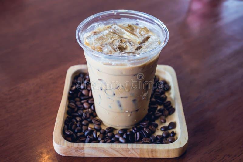 Milk-shake ou frappuccino froid de boissons de café dans le plateau en bois avec le grain de café image libre de droits