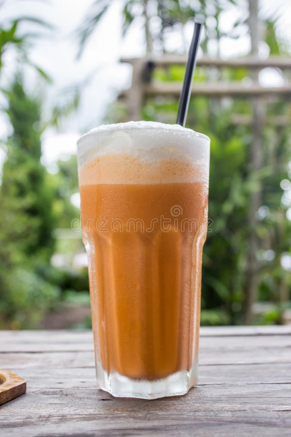 Milk-shake thaïlandais de thé avec du lait blanc de crème ou de vapeur sur la table en bois photographie stock libre de droits