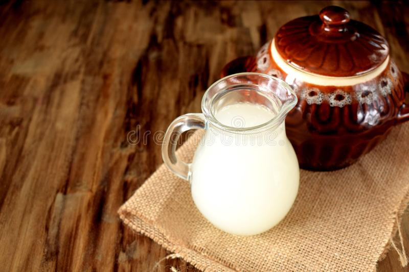 Milk whey in a glass jug and a clay pot. In the background royalty free stock photography