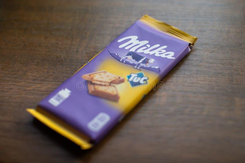 """Milka czekoladowy bar z Tuc krakersem z drewnianym tłem Milka jest gatunkiem czekoladowa słodycze MondelÄ """"z zawody międzynarodow zdjęcie stock"""