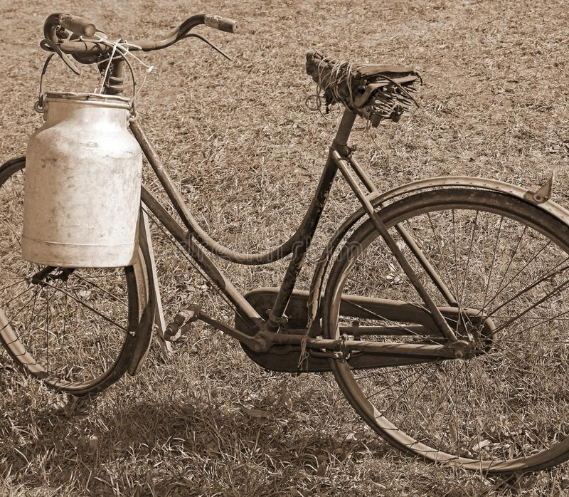 Milking bike with bin for milk transport sepia effect royalty free stock photography