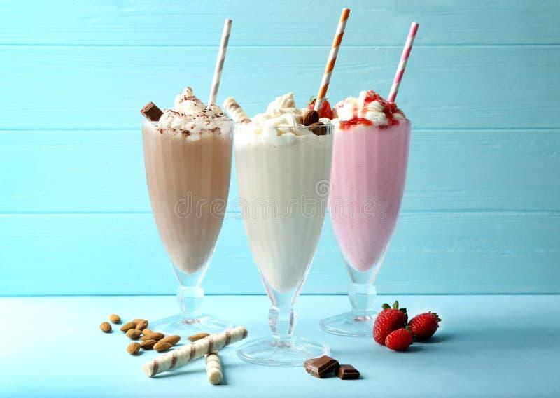 Milks shake deliciosos no fundo azul imagem de stock royalty free