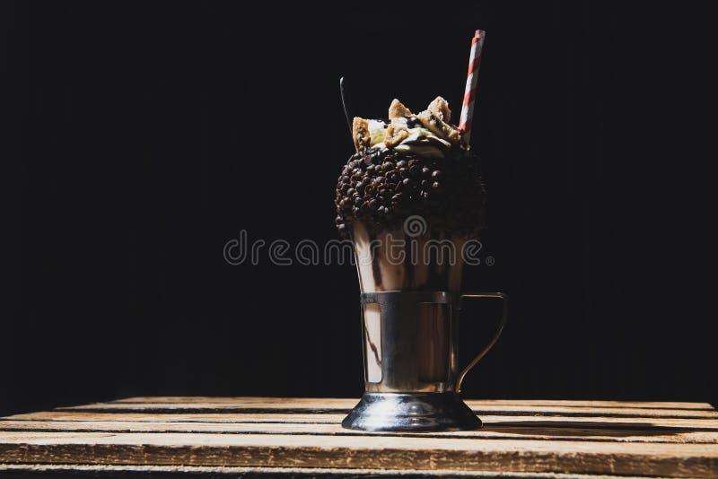 Milkshake που καλύπτεται με τα κομμάτια σοκολάτας Μαύρο υπόβαθρο στοκ εικόνες με δικαίωμα ελεύθερης χρήσης