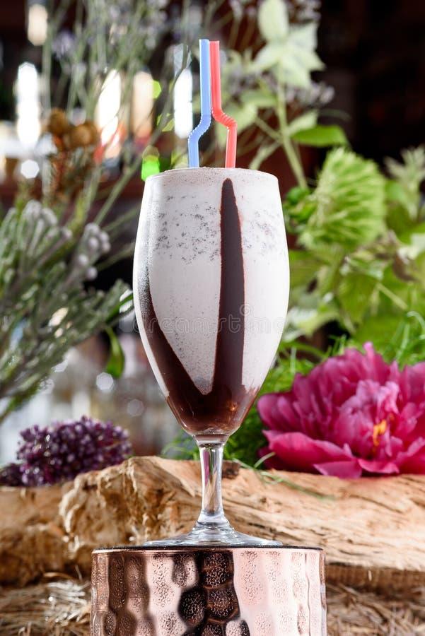 Milkshake στο όμορφο γυαλί στο υπόβαθρο των φρέσκων λουλουδιών Θερινό ποτό στοκ εικόνα με δικαίωμα ελεύθερης χρήσης