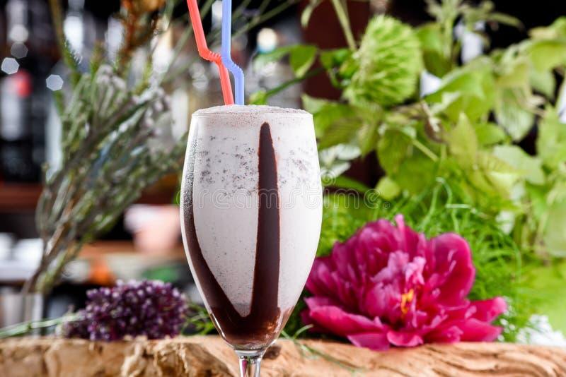Milkshake στο όμορφο γυαλί στο υπόβαθρο των φρέσκων λουλουδιών Θερινό ποτό στοκ εικόνες