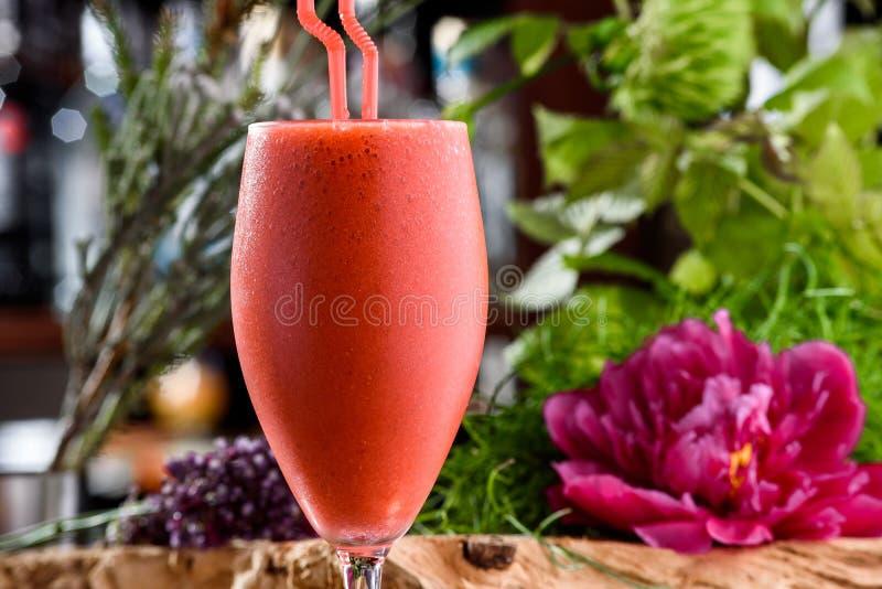 Milkshake στο όμορφο γυαλί στο υπόβαθρο των φρέσκων λουλουδιών Θερινό ποτό στοκ εικόνες με δικαίωμα ελεύθερης χρήσης