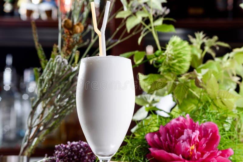 Milkshake στο όμορφο γυαλί στο υπόβαθρο των φρέσκων λουλουδιών Θερινό ποτό στοκ φωτογραφίες