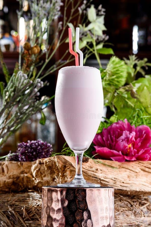Milkshake στο όμορφο γυαλί στο υπόβαθρο των φρέσκων λουλουδιών Θερινό ποτό στοκ εικόνα