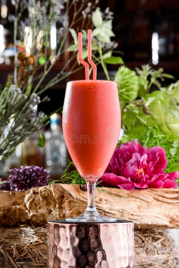 Milkshake στο όμορφο γυαλί στο υπόβαθρο των φρέσκων λουλουδιών Θερινό ποτό στοκ φωτογραφία με δικαίωμα ελεύθερης χρήσης