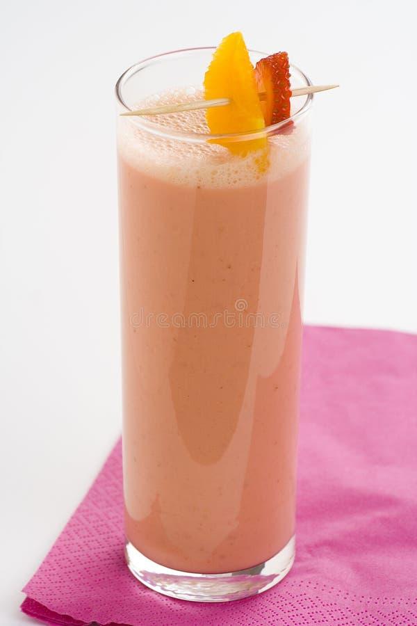 Milkshake alaranjado da banana da morango deliciosa foto de stock