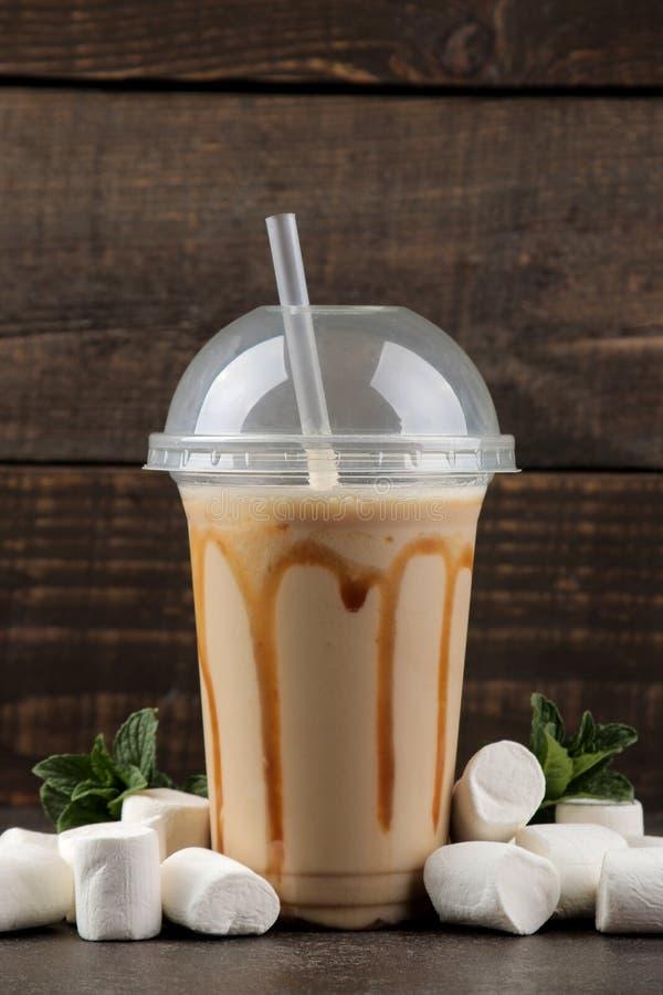 Milkshake de chocolat dans un verre en plastique avec le sirop, et les guimauves et la menthe sur un fond brun photo stock