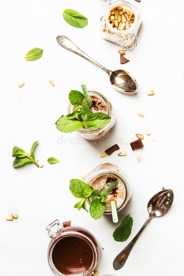 Milkshake de chocolat ou cocktail de lait avec l'écrimage, la menthe verte et les écrous de cèdre, table de cuisine blanche, l'es photo libre de droits