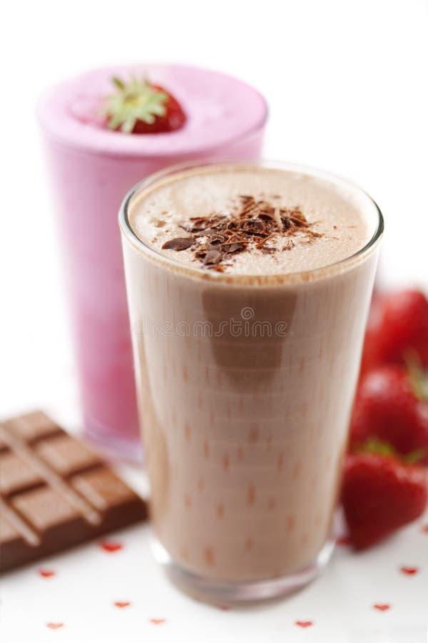 Milkshake del chocolate y de la fresa fotos de archivo