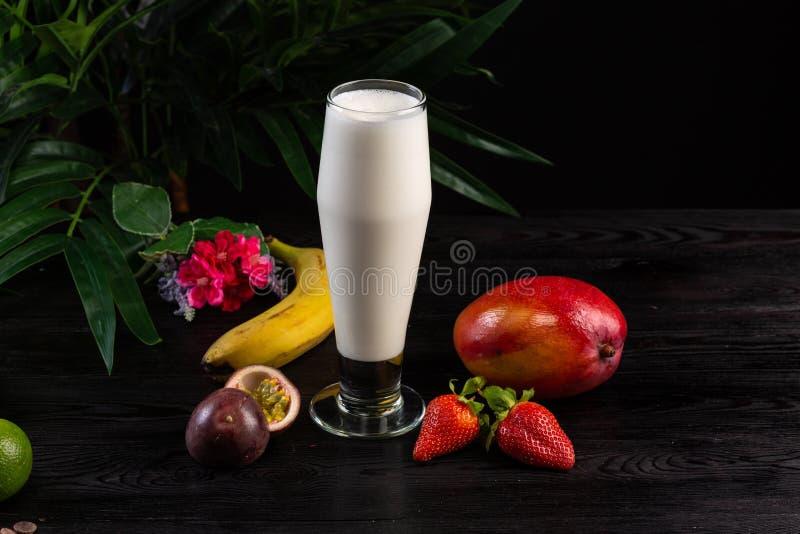 Milkshake in een lang glas en vruchten op een donkere achtergrond royalty-vrije stock afbeeldingen