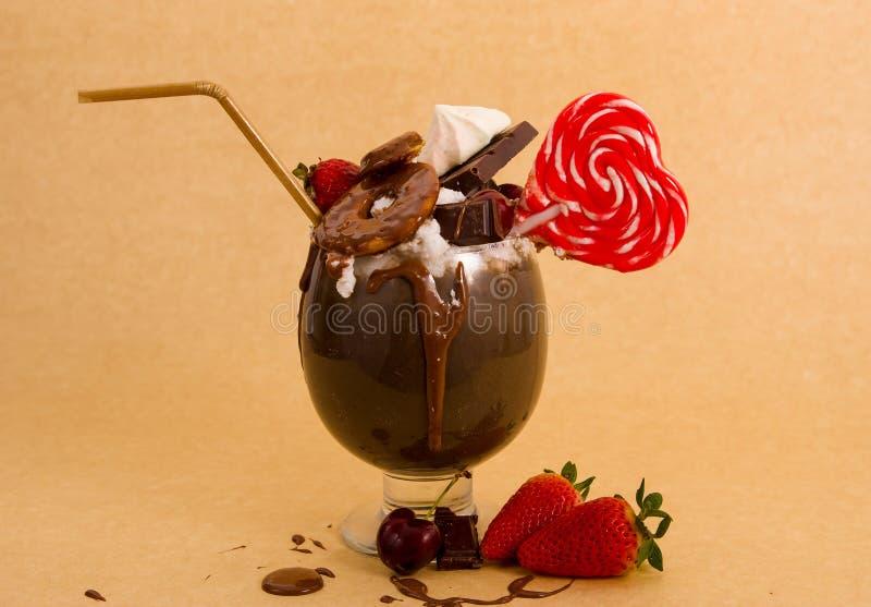 Milkshake extrême indulgent de chocolat avec le gâteau de 'brownie', fraises, cerises, sucrerie avec la forme de coeur, une paill photos libres de droits