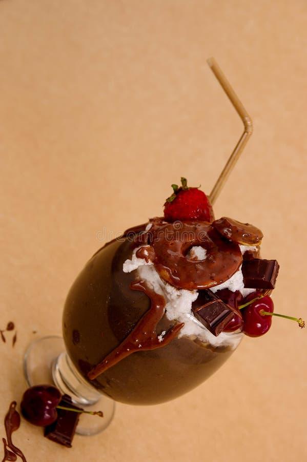 Milkshake extrême indulgent de chocolat avec le gâteau de 'brownie', les fraises, les cerises, et une paille en plastique avec la photo libre de droits