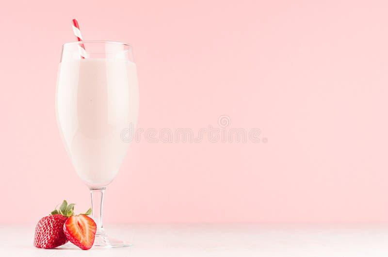 Milkshake frais de fraise avec la paille et la baie juteuse de tranche dans l'intérieur rose mol gracieux doux, l'espace de copie photo stock