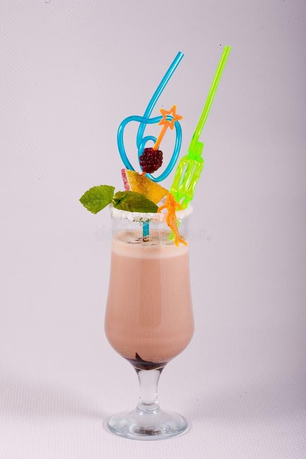 Milkshake i ett exponeringsglas dekorerade med bäret, choklad och mintkaramellen arkivbilder