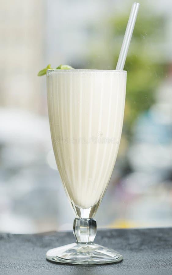 Milkshake i ett stort exponeringsglas med ett rör dekorerade med mintkaramellen ovanför sikt bakgrundsblurblomma inom som looks s royaltyfria bilder