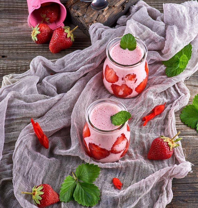 Milkshake med den nya jordgubben i exponeringsglaskrus royaltyfria foton