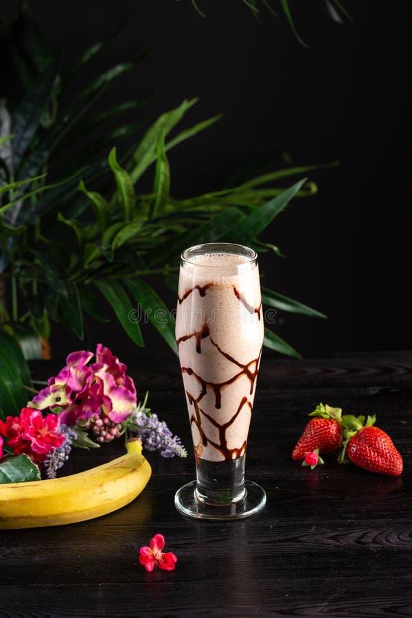 Milkshake met banaan en chocolade in een lang glas op een donkere achtergrond stock foto