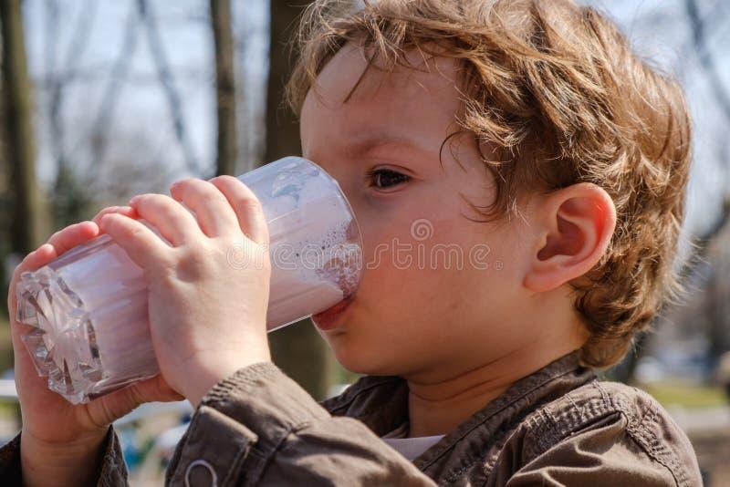 Milkshake potable de fraise de petit garçon image stock