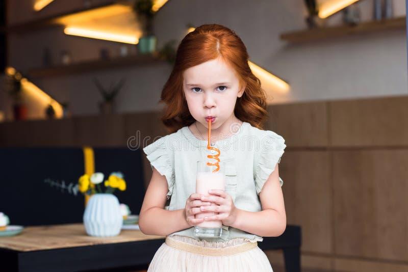 milkshake potable de petite fille d'une chevelure rouge mignonne de verre et regarder l'appareil-photo photo libre de droits
