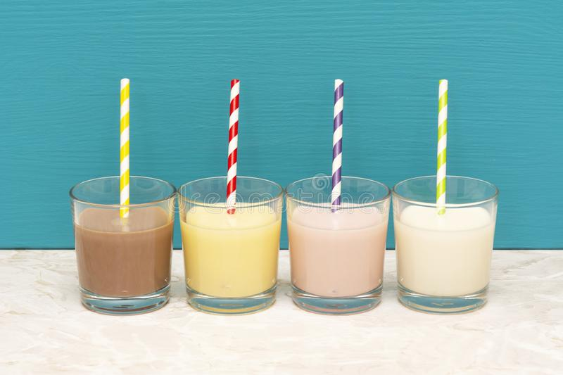 Milkshakes και φρέσκο γάλα με τα αναδρομικά άχυρα εγγράφου στους ανατροπείς γυαλιού στοκ εικόνες