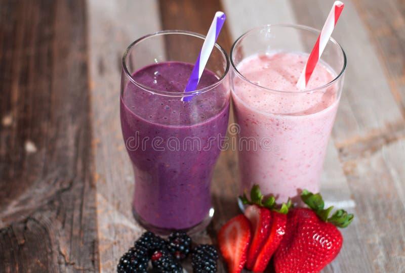 Milkshakes που γίνεται με τα φρέσκες βακκίνια και τις φράουλες σε ένα γυαλί στοκ εικόνες