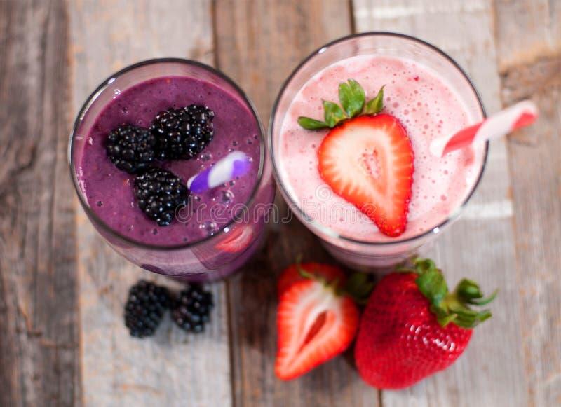 Milkshakes που γίνεται με τα φρέσκες βακκίνια και τις φράουλες σε ένα γυαλί στοκ φωτογραφίες με δικαίωμα ελεύθερης χρήσης