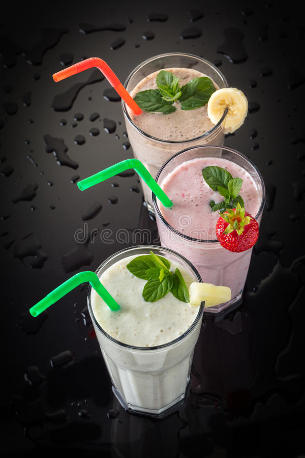 Milkshakes on a black background. And drops of water stock photos