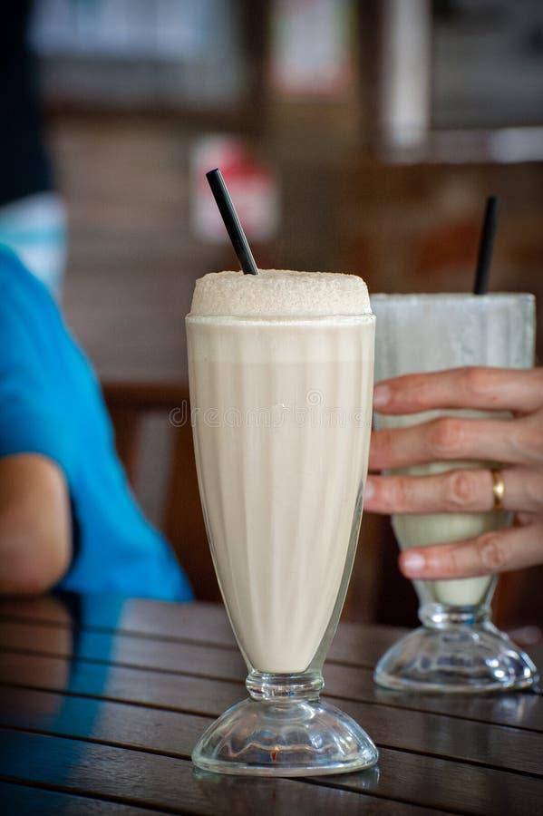 Milkshakes na stole wokoło pić obrazy stock